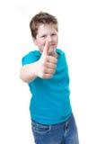 Éxito en escuela. El muchacho sonriente del alumno manosea con los dedos para arriba - aislado en whi Foto de archivo