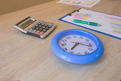 Éxito, motivación, flujos financieros reloj grande, calculadora, pluma, gráficos de negocio en la tabla Fotos de archivo