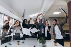 Éxito y concepto que gana - equipo feliz del negocio que celebra la victoria en oficina imagen de archivo libre de regalías