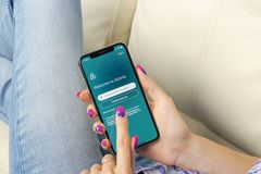 Ícone da aplicação de Airbnb na tela do iPhone X de Apple em hsnds da mulher Ícone de Airbnb app Airbnb COM é Web site em linha p Imagem de Stock Royalty Free