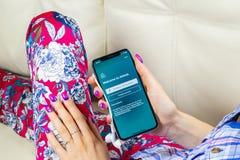 Ícone da aplicação de Airbnb na tela do iPhone X de Apple em hsnds da mulher Ícone de Airbnb app Airbnb COM é Web site em linha p Foto de Stock