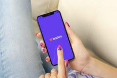 Ícone da aplicação de Badoo na tela do iPhone X de Apple nas mãos da mulher Ícone de Badoo app Badoo é uma rede social em linha d Foto de Stock Royalty Free