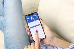 Ícone da aplicação de Facebook no close-up da tela do smartphone do iPhone X de Apple nas mãos da mulher Ícone de Facebook app Íc Fotos de Stock Royalty Free