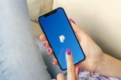 Ícone da aplicação de Paypal na tela do smartphone do iPhone X de Apple nas mãos da mulher Ícone de Paypal app Paypal é um financ Imagens de Stock