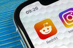 Ícone da aplicação de Reddit no close-up da tela do smartphone do iPhone X de Apple Ícone de Reddit app Reddit é uma rede social  Imagem de Stock Royalty Free
