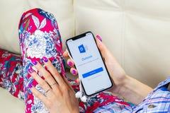 Ícone da aplicação do escritório de Microsoft Outlook na tela do iPhone X de Apple na mão da mulher Ícone de Microsoft Outlook ap foto de stock