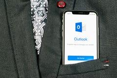 Ícone da aplicação do escritório de Microsoft Outlook no close-up da tela do iPhone X de Apple no bolso do revestimento Ícone de  foto de stock royalty free