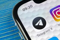 Ícone da aplicação do telegrama X no close-up da tela do iPhone X de Apple Ícone do telegrama X app O telegrama X é uma rede soci Fotos de Stock Royalty Free