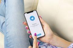 Ícone da aplicação do telegrama no close-up da tela do iPhone X de Apple nas mãos da mulher Ícone do app do telegrama O telegrama Fotografia de Stock Royalty Free