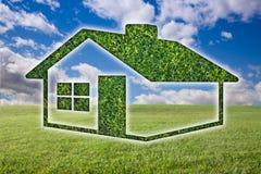 Ícone da casa da grama verde sobre o campo, o céu e as nuvens Foto de Stock Royalty Free