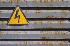 Ícone de advertência da tensão em uma estrutura oxidada Fotos de Stock Royalty Free