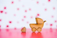 Ícone de madeira do carrinho de bebê e do pouco coração no CCB cor-de-rosa e branco Fotografia de Stock