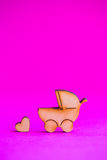 Ícone de madeira do carrinho de bebê e do pouco coração no fundo carmesim Fotografia de Stock