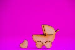 Ícone de madeira do carrinho de bebê e do pouco coração no fundo carmesim Imagem de Stock