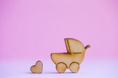 Ícone de madeira do carrinho de bebê e do pouco coração no fundo cor-de-rosa Imagens de Stock