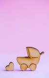 Ícone de madeira do carrinho de bebê e do pouco coração no fundo cor-de-rosa Fotos de Stock