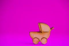Ícone de madeira do carrinho de bebê no fundo carmesim Imagem de Stock Royalty Free