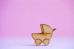 Ícone de madeira do carrinho de bebê no fundo cor-de-rosa Imagens de Stock Royalty Free