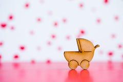 Ícone de madeira do carrinho de bebê no fundo cor-de-rosa e branco Imagem de Stock Royalty Free