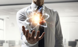 Ícone do átomo na palma imagens de stock royalty free