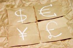 Ícones da moeda do dólar, do euro, da libra e dos ienes no papel Fotografia de Stock Royalty Free