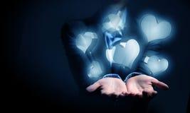 Ícones de vidro do coração na palma Imagens de Stock