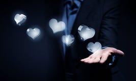 Ícones de vidro do coração na palma Imagens de Stock Royalty Free