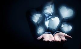 Ícones de vidro do coração na palma Imagem de Stock Royalty Free