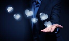 Ícones de vidro do coração na palma Imagem de Stock