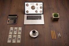 Ícones do gráfico da carta de torta na tela do portátil com acessórios do escritório Fotos de Stock
