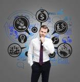Ícones pensativos do homem e do dinheiro na parede cinzenta Fotos de Stock Royalty Free