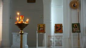 Ícones sagrados na igreja no fundo de sinos ardentes vídeos de arquivo