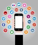 Ícones sociais dos meios com a mão que guarda Smartphone Fotos de Stock Royalty Free