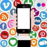 Ícones sociais dos meios com a mão que guarda Smartphone 2 Imagens de Stock Royalty Free