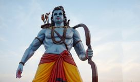 Ídolo hindu de Sri Rama do deus com curva e setas na pose de combate, contra o céu azul foto de stock royalty free