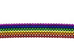 Ímã colorido das esferas na linha do arco-íris em um contexto branco Fotografia de Stock Royalty Free