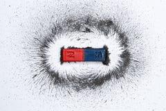 Ímã de barra com campo magnético do pó do ferro no fundo branco Conceito da ciência imagens de stock royalty free