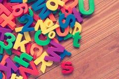Ímãs coloridos do brinquedo no fundo de madeira Imagem de Stock
