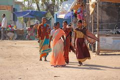 Índia, Hampi, o 2 de fevereiro de 2018 As mulheres em saris brilhantes andam abaixo da rua e do sorriso Mulheres indianas fotos de stock