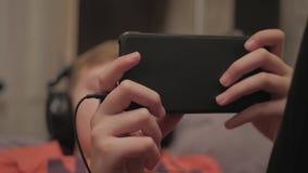 Índice de observação dos meios do menino usando fones de ouvido e app do telefone celular que encontra-se no sofá em casa Feche a filme