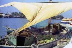 ÍSQUIO, ITÁLIA, 1975 - um shipman ilumina um cigarro na máscara da vela de suas melancias levando do barco no porto dos ísquios imagens de stock royalty free