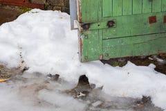 Άκρη μιας πράσινης ξύλινης πόρτας snowdrift στοκ φωτογραφία με δικαίωμα ελεύθερης χρήσης