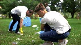 Άνθρωποι που παίρνουν τα σκουπίδια στη πλαστική τσάντα, πρόβλημα επεξεργασίας αποβλήτων, ανακύκλωση στοκ εικόνα