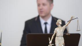 Άνδρας και γυναίκα που συσκέπτονται με τον επαγγελματικό δικηγόρο Άγαλμα Themis στο δικηγορικό γραφείο απόθεμα βίντεο