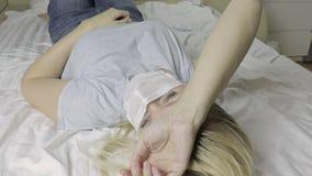 Άρρωστη γυναίκα με την ιατρική μάσκα στο πρόσωπο που βρίσκεται στο κρεβάτι και το βάσανο φιλμ μικρού μήκους