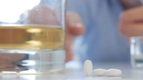 Άρρωστο πρόσωπο που παίρνει τα χάπια και τα φάρμακα με το οινόπνευμα και τα τσιγάρα απόθεμα βίντεο