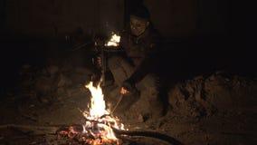 Άσχημη επικίνδυνη συνεδρίαση τεράτων zombie κοντά στη φωτιά με το βαρύ διαγώνιο τόξο στο σκοτεινό συγκεκριμένο καταφύγιο φρίκη απόθεμα βίντεο