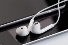 Άσπρα ακουστικά στην ταμπλέτα και το τηλέφωνο στοκ φωτογραφία