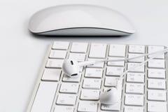Άσπρα ακουστικά στο άσπρο πληκτρολόγιο στοκ φωτογραφία