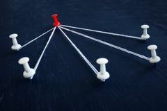 Άσπρες καρφίτσες και κόκκινο ένα ώθησης που συνδέονται με το νήμα Ηγεσία, διαχείριση και εξουσιοδότηση στοκ εικόνα